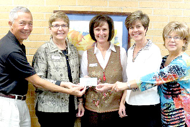 A scholarship check from Suzanne's readings is presented to the administrators of Lake Technical Center in Eustis, Florida.